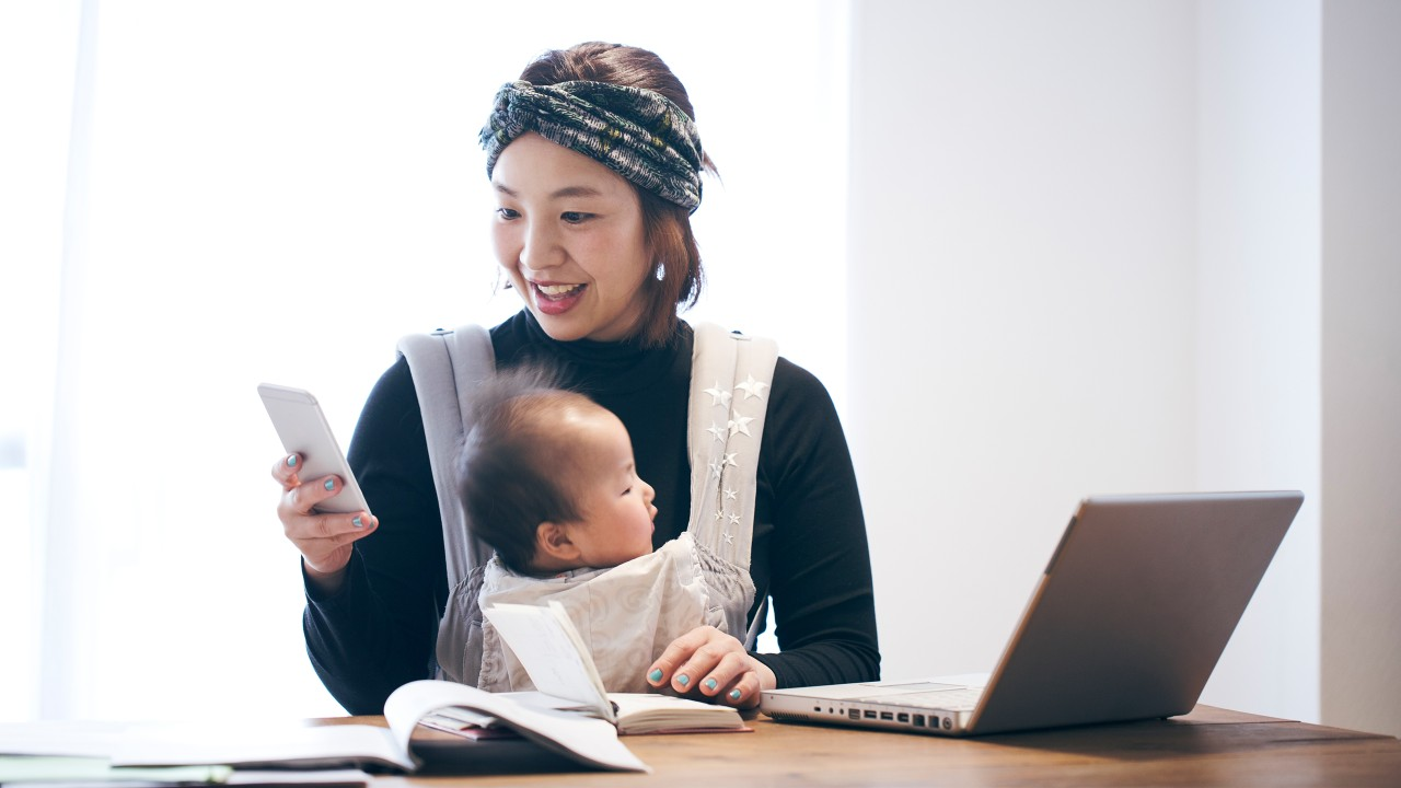 Mother with baby working at home; image used for HSBC Malaysia Remote Engagement Service page.