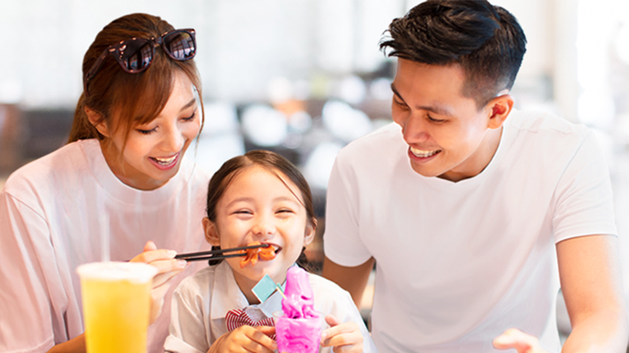 A father watches his wife feeding their daughter; image used for HSBC Malaysia credit card cash back offer