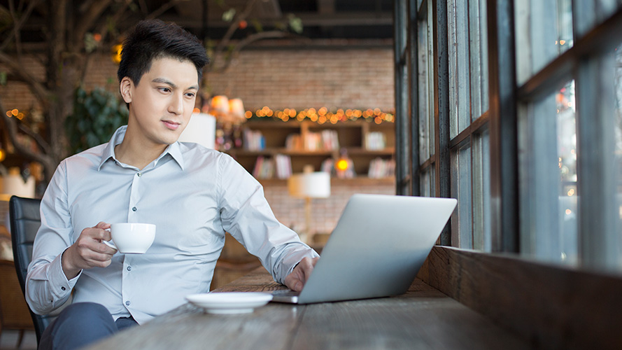 Man using laptop in cafe; image used for HSBC Amanah Term Deposit-i.