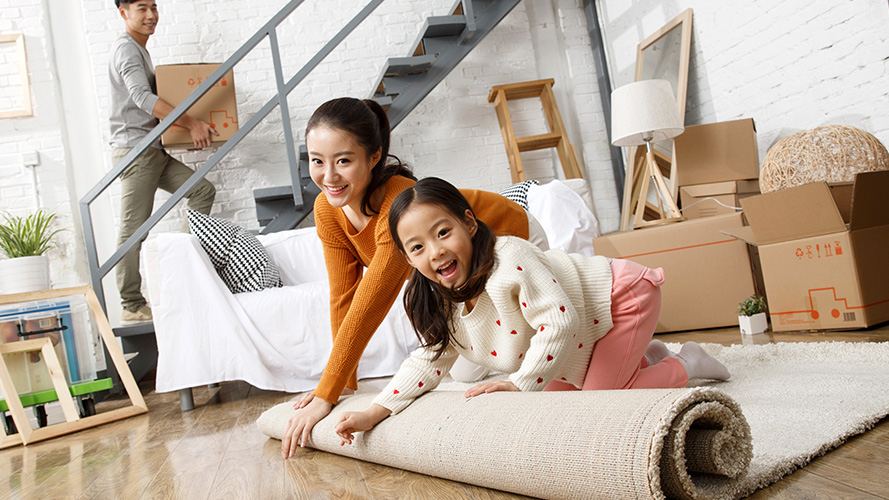 Woman and child unrolling carpet in living room, man holding box walking up stairs
