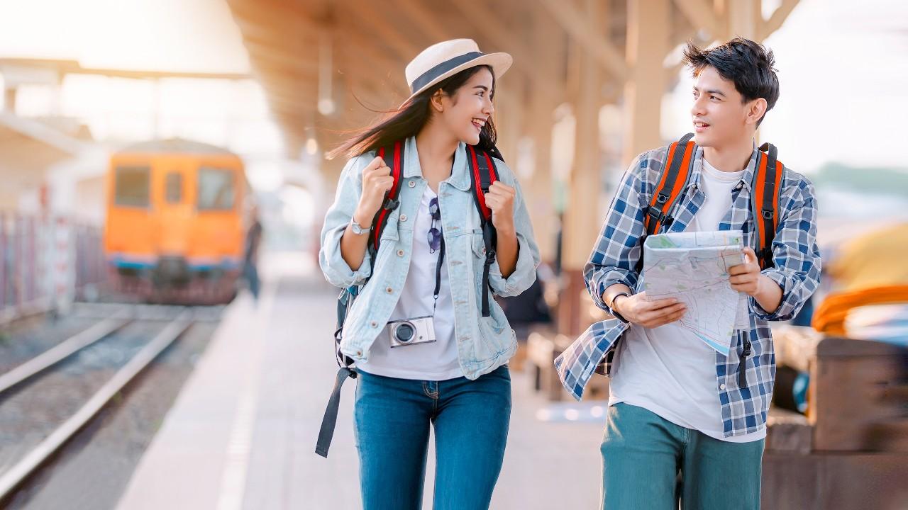 A couple of tourists at a train platform; image used for HSBC Malaysia JomPAY page.