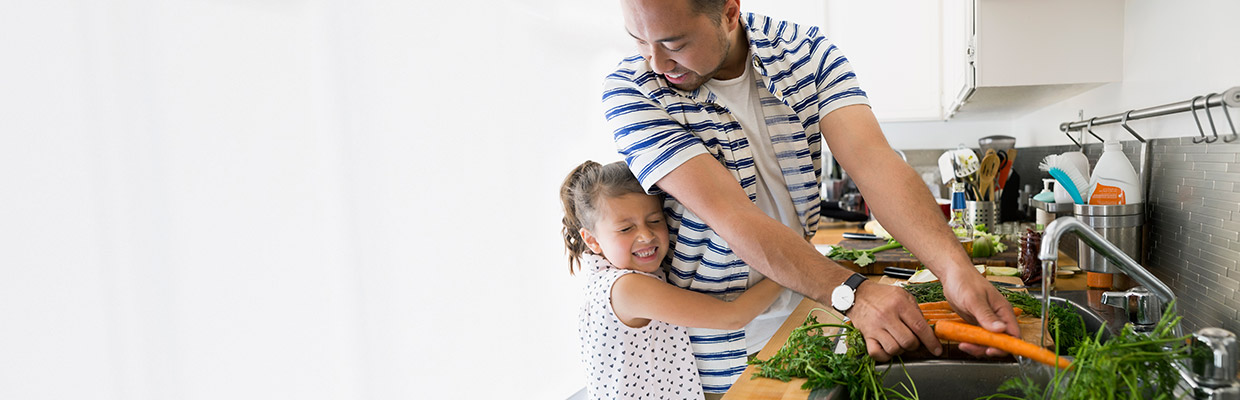 A father and daughter are cooking together; image used for HSBC Malaysia Protection