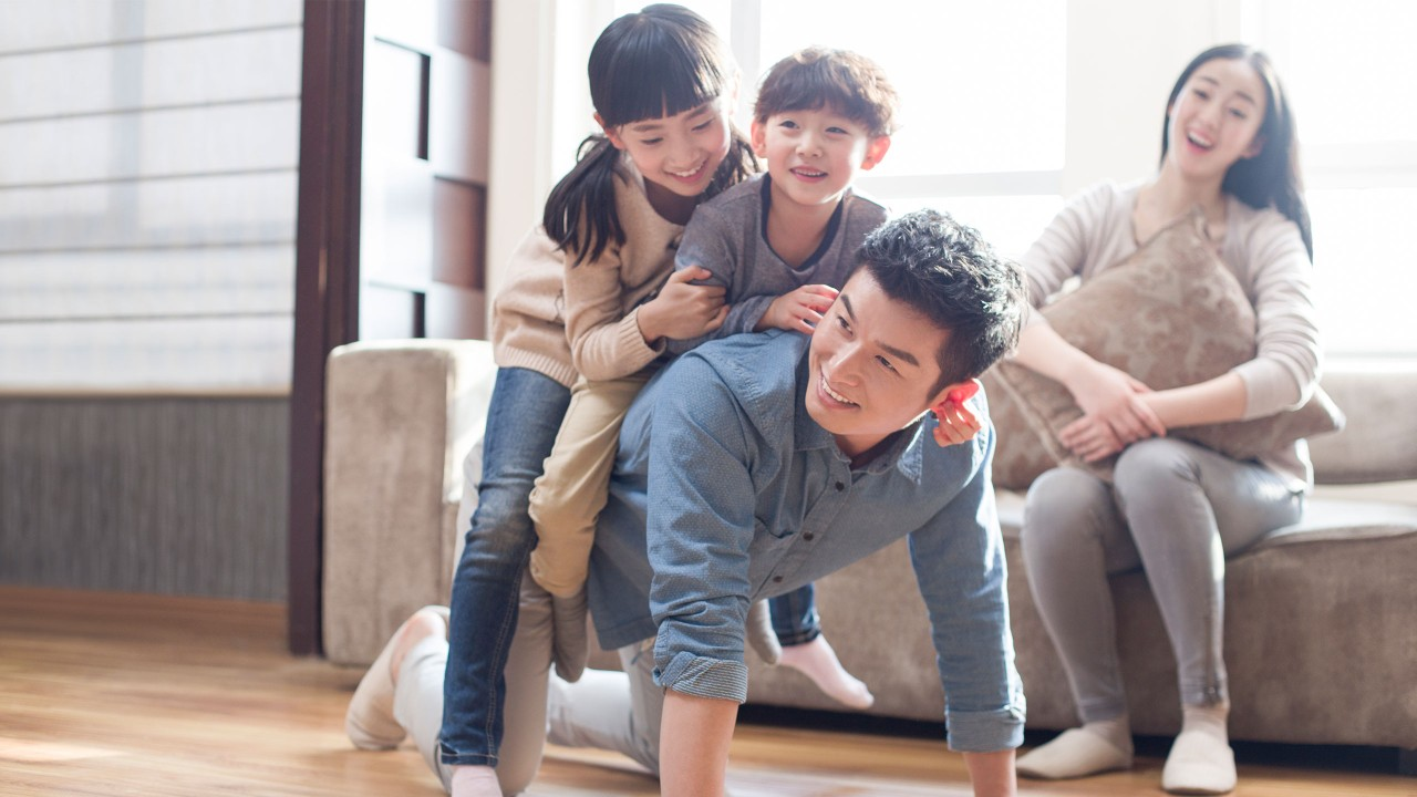 Happy family is playing piggyback ride at home; image used for HSBC Malaysia Cash Instalment Plan page.
