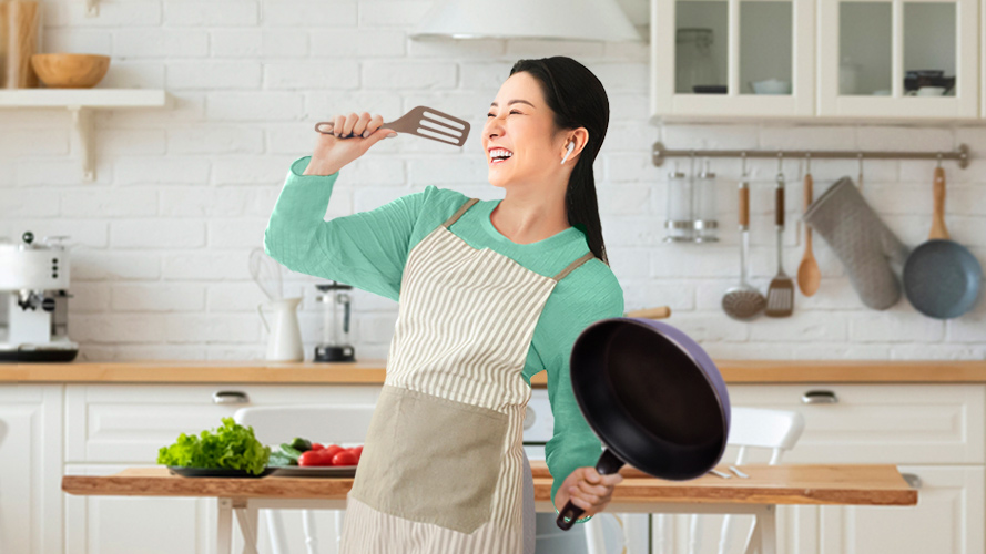 A woman is standing in the kitchen; image used for HSBC Malaysia cash back promotion page.