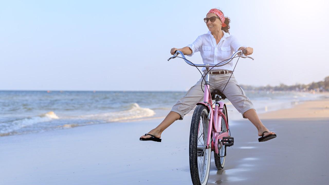 Woman riding bike; image used for HSBC's UniversalTreasure Plus Plan page.