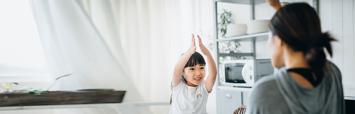 A mother and her little daughter are having fun while having breakfast together; image used on HSBC Malaysia Smart Home Cover page.