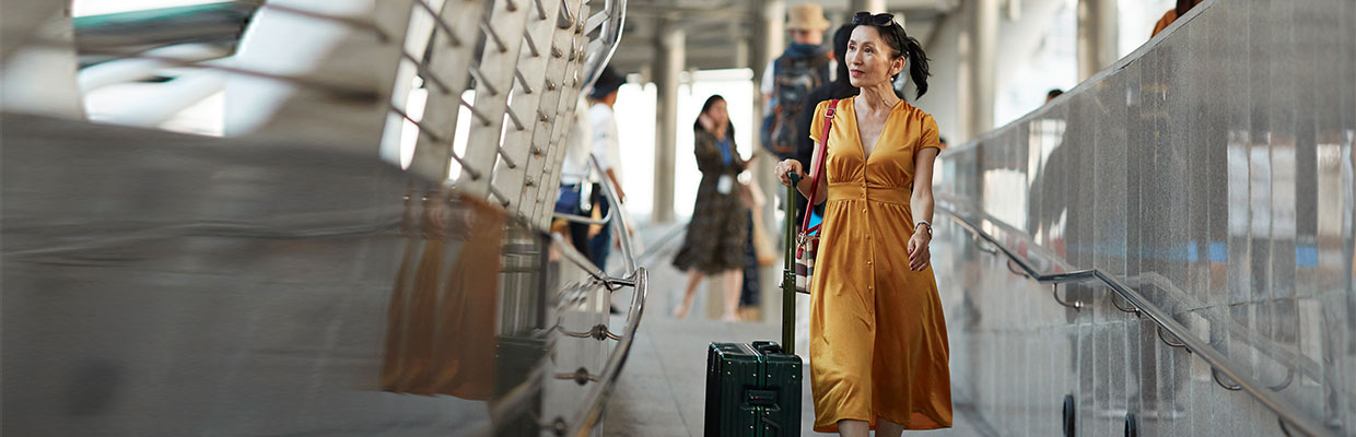 A woman is walking on the street with a luggage; image used on HSBC Malaysia travel care page.