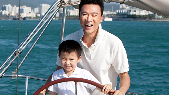 A father is sailing a boat with his son; image used for HSBC Malaysia Structured Investment page