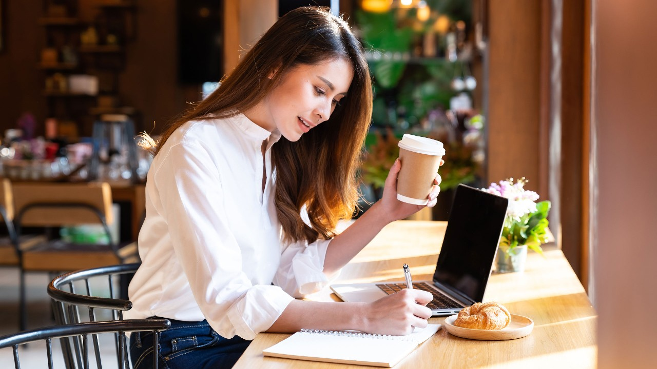 Woman using laptop at cafe shop; image used on HSBC Malaysia foreign exchange page.