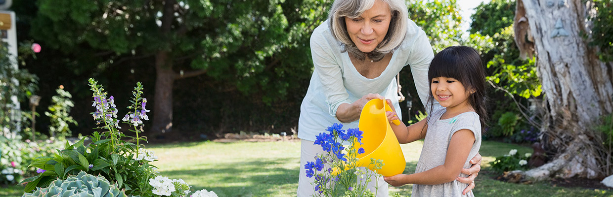 A grandmother and granddaughter are watering flowers; image used for HSBC Malaysia Second Home Mortgage