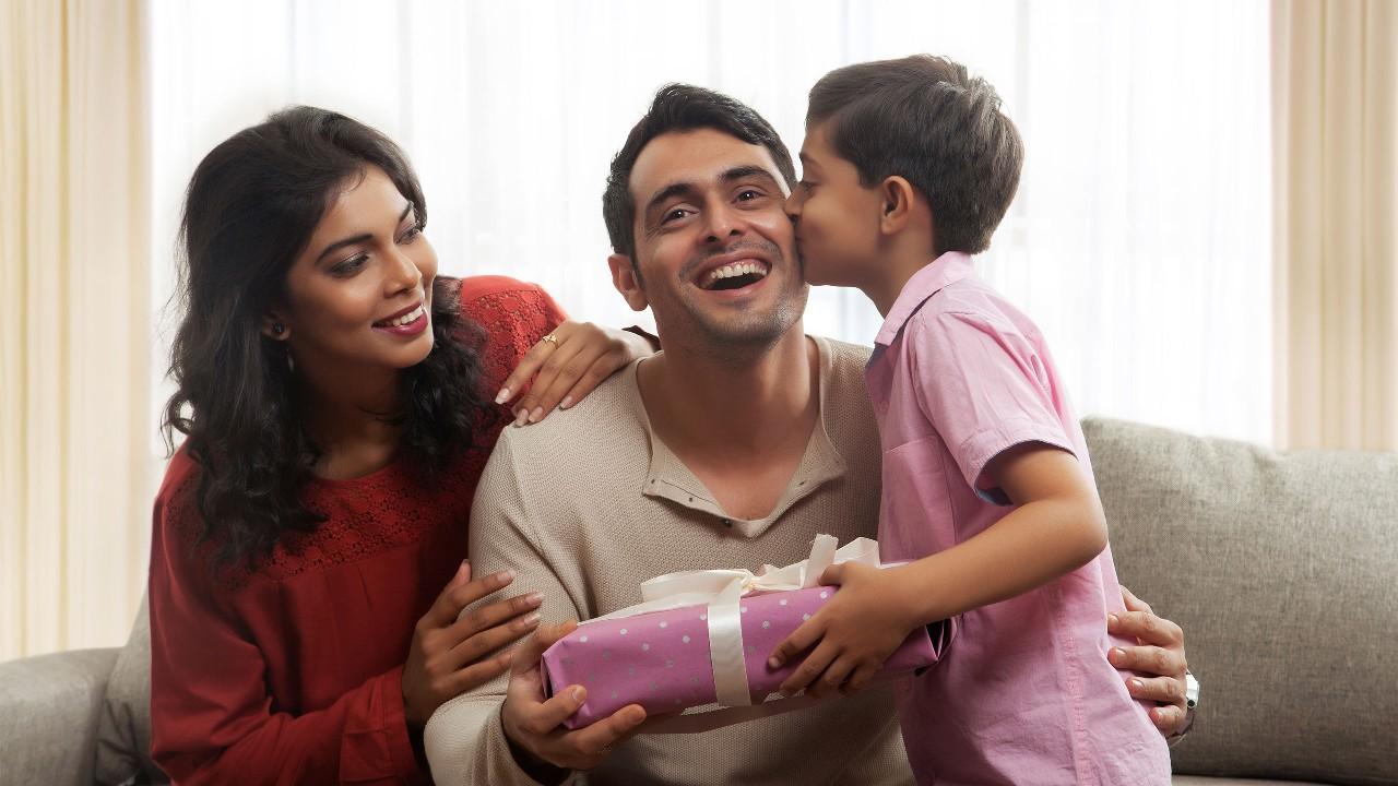 Son kissing father and giving gift;  image used for HSBC Malaysia Amanah Got a Big Hari Raya Credit Card Bill article