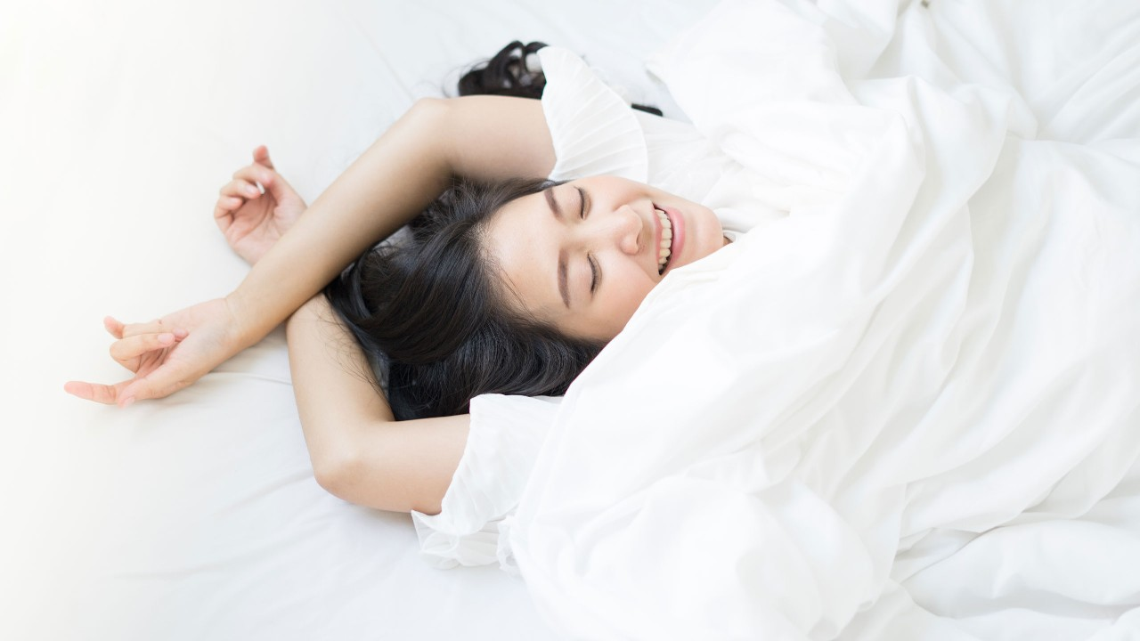 A woman is lying in bed; image used for HSBC Malaysia Fusion 'Work life balance for small business owners' article page.