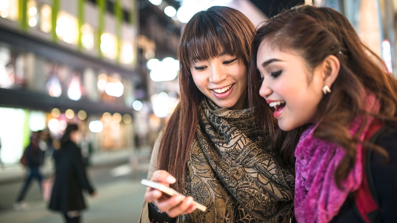 Two girls are looking at the same mobile phone on the street; image used for HSBC Malaysia DuitNow page.